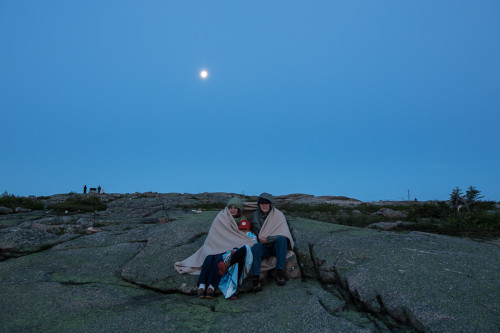 A family huddles under a blanket on top of Cadillac Mountain waiting for sunrise as the moon sets behind them.