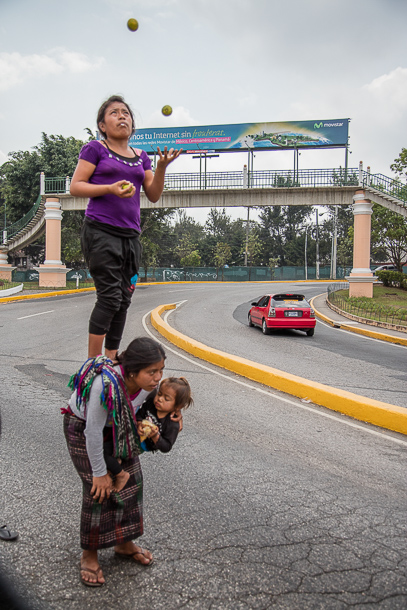 A mom and her kids perform at a busy Guatemala City street corner hoping for tips.